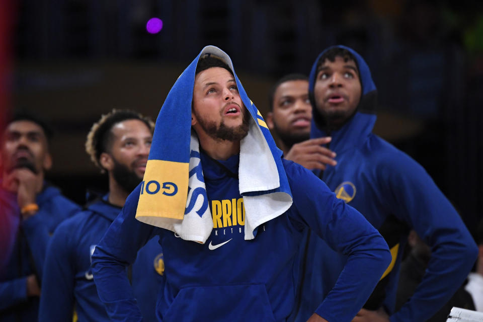 Golden State Warriors guard Stephen Curry looks at a replay along with teammates during the second half of a preseason NBA basketball game against the Los Angeles Lakers Wednesday, Oct. 16, 2019, in Los Angeles. The Lakers won 126-93. (AP Photo/Mark J. Terrill)
