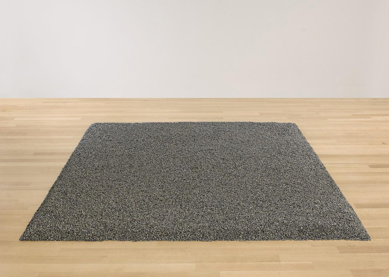 """This undated photo provided by Sotheby's New York shows """"Sunflower Seeds,"""" a sculpture by Chinese dissident artist Ai Weiwei featuring one ton of handmadeporcelain sunflower seeds. The sculpture , is slated to be auctioned by Sotheby's on Wednesday, May 9, 2012 . The sackful of hand-painted ceramic seeds, which can be arranged in a myriad of shapes, is estimated to go for $600,000 to $800,000. (AP Photo/Sotheby's)"""