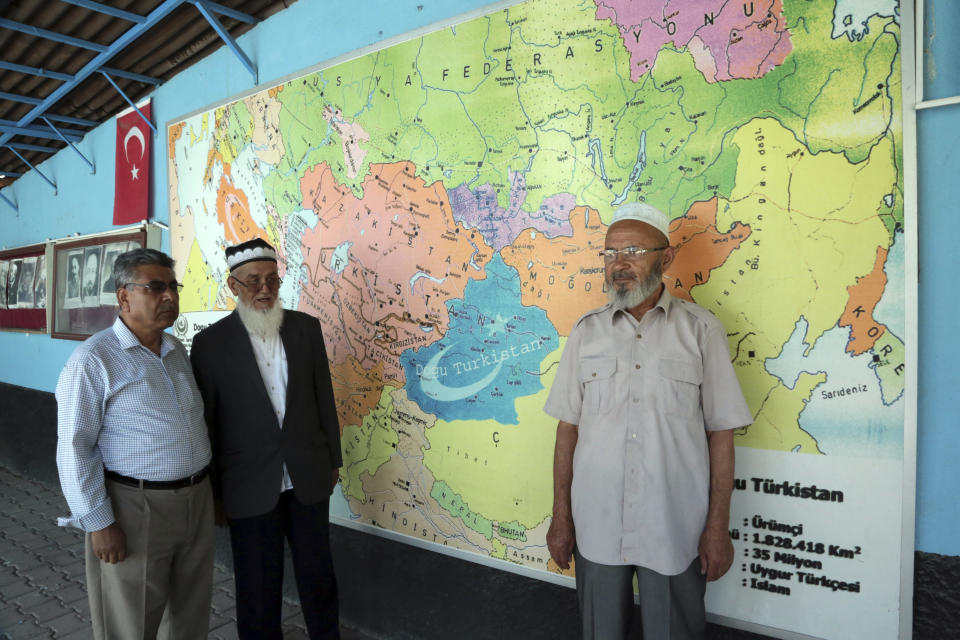 """FILE - In this Aug. 8, 2017, file photo, Uighur Muslim men stand in front of map showing the area claimed by Uighur separatists as """"East Turkistan"""" marked in blue at a resettlement community in Kayseri in central Turkey. In the U.S. departure from Afghanistan, China has seen the realization of long-held hopes for a reduction of the influence of a geopolitical rival in what it considers its backyard. Yet, it is also deeply concerned that the very withdrawal could bring instability to that backyard - Central Asia - and possibly even spill over the border into China itself in its heavily Muslim northwestern region of Xinjiang. (AP Photo/Burhan Ozbilici, File)"""