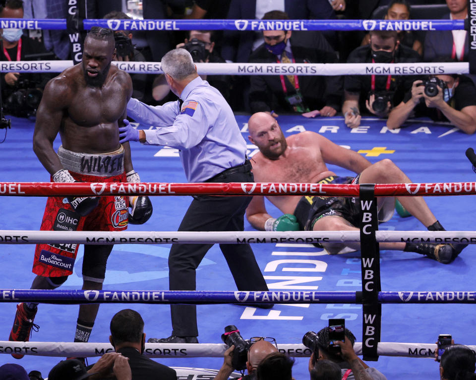 Referee Russell Mora moves Deontay Wilder (pictured left) away from Tyson Fury (pictured right) who is on the floor after a knockdown.