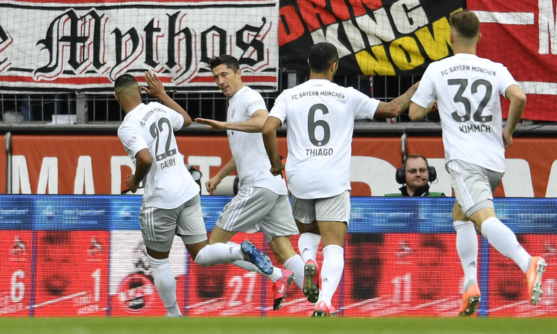 Bayern's Robert Lewandowski, 2nd from left, is celebrated after scoring the opening goal during the German Bundesliga soccer match between 1. FC Cologne and Bayern Munich in Cologne, Germany, Sunday, Feb. 16, 2020. (AP Photo/Martin Meissner)