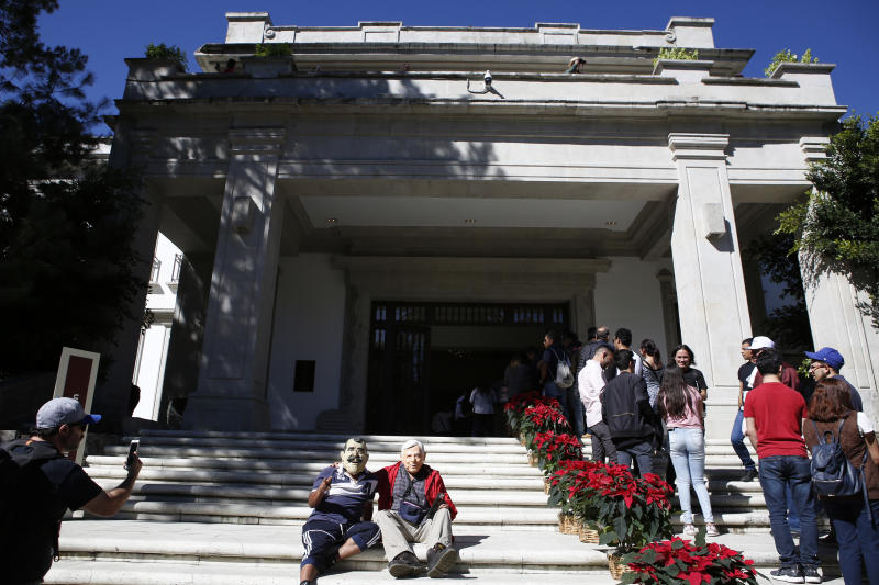 Enedino Camarillo, who wears a mask representing former Mexican President Vicente Fox, and Luis Duque wearing a mask depicting Andres Manuel Lopez Obrador, sit on the front steps of the Casa Miguel Aleman, the presidential residence know as Los Pinos, in Mexico City, Saturday, Dec. 1, 2018. A few hundred people showed up for the opening of the compound, known as Los Pinos; it was closed for so long that many people don't know where the entrances are. (AP Photo/Ginnette Riquelme)