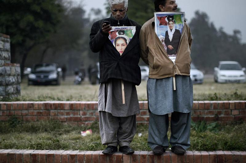Supporters of Pakistan's slain leader Benazir Bhutto, one listens to speeches, right, and the other checks his mobile phone, at a ceremony to mark the fifth anniversary of her death, in Islamabad, Pakistan, Thursday, Dec. 27, 2012. The 24-year-old son of former Pakistani Prime Minister Benazir Bhutto has launched his political career with a fiery speech on the fifth anniversary of his mother's assassination. (AP Photo/Muhammed Muheisen)