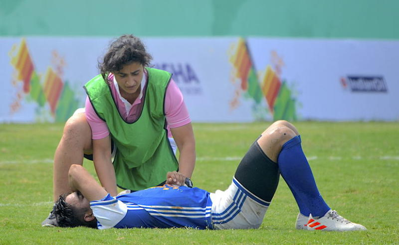 Indian women's team rugby captain Vahbiz Bharucha tends to an injured player on Wednesday in her capacity as a physiotherapist during the Khelo India University Games being held in Bhubaneswar. Image courtesy: Khelo India University Games