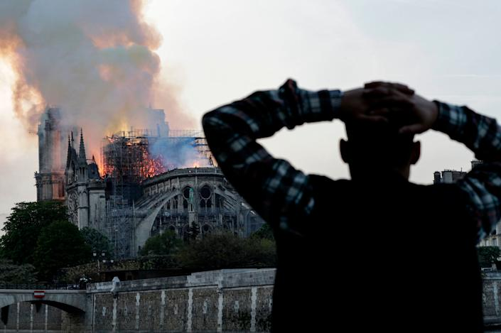 A man watches the landmark Notre-Dame Cathedral burn, engulfed in flames, in central Paris on April 15, 2019. (Photo: Geoffroy Van Der Hasselt/AFP/Getty Images)