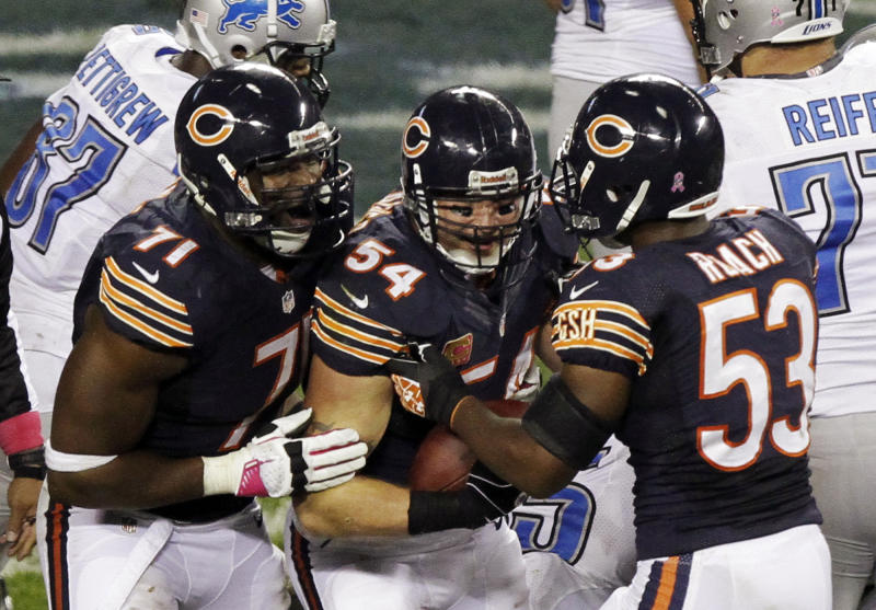 Chicago Bears linebacker Brian Urlacher (54) celebrates with Israel Idonije (71) and Nick Roach (53) after he recovered fumble against the Detroit Lions near the goal line in the second half of an NFL football game in Chicago, Monday, Oct. 22, 2012. (AP Photo/Kiichiro Sato)