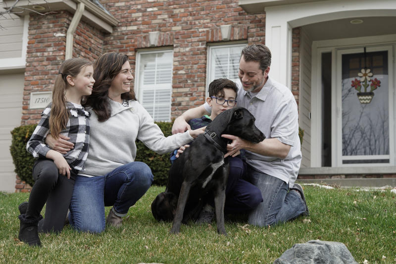 In this March 27, 2020, photo, Kim Simeon; her husband, Adam; and children, Annabel, 9, and Brennan, 11, pose for a photo with Nala, a dog they are fostering, in Omaha, Neb. The Simeon family was headed home to Omaha from a much-needed Smoky Mountains vacation when Kim Simeon spotted a social media post from the Nebraska Humane Society, pleading with people to consider fostering a pet.  (AP Photo/Nati Harnik)