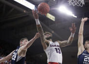 Gonzaga guard Josh Perkins (13) shoots between BYU guard McKay Cannon (24) and forward Gavin Baxter during the first half of an NCAA college basketball game in Spokane, Wash., Saturday, Feb. 23, 2019. (AP Photo/Young Kwak)