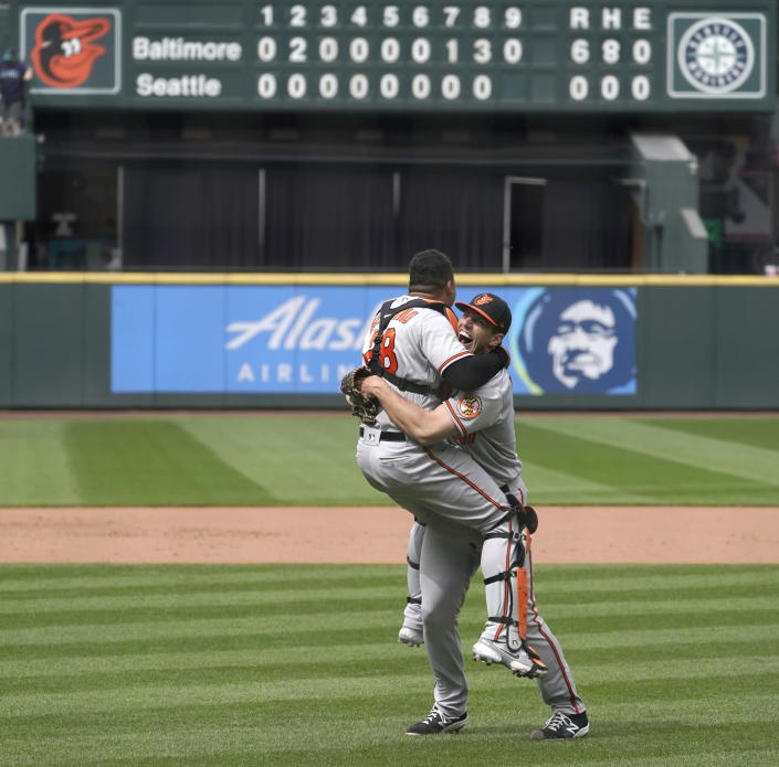 Baltimore Orioles starting pitcher John Means, right, hugs catcher Pedro Severino after Means threw a no-hitter baseball game against the Seattle Mariners, Wednesday, May 5, 2021, in Seattle. The Orioles won 6-0. (AP Photo/Ted S. Warren)