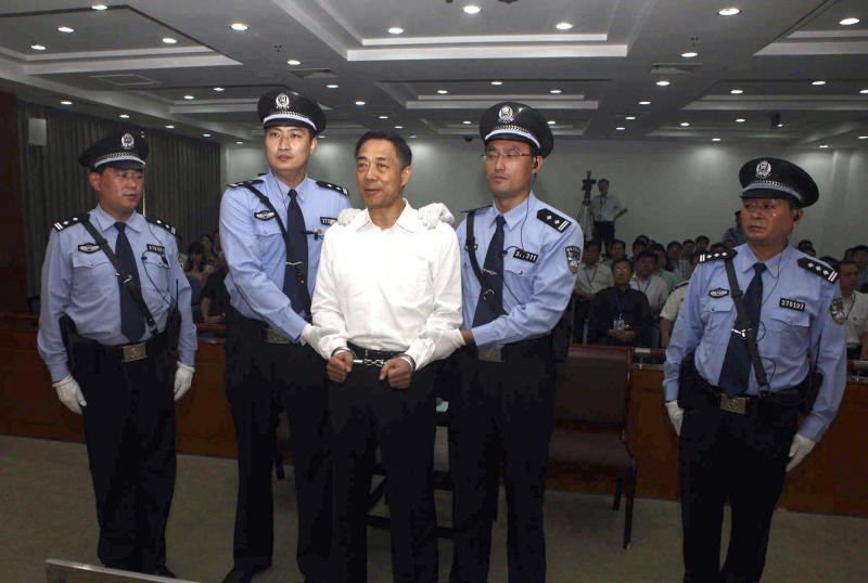 In this photo released by the Jinan Intermediate People's Court, fallen politician Bo Xilai, center, is handcuffed and held by police officers as he stands at the court in Jinan, in eastern China's Shandong province Sunday, Sept. 22, 2013. The Chinese court convicted Bo on charges of taking bribes, embezzlement and abuse of power and sentenced him to life in prison, capping one of the country's most lurid political scandals in decades. (AP Photo/Jinan Intermediate People's Court)