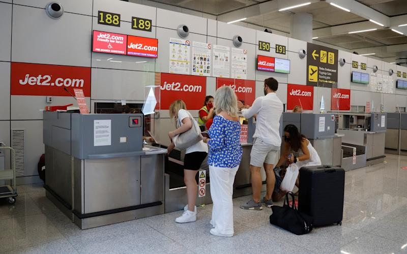 Passengers queue up at the Jet2 check-in desk at Palma de Mallorca airport - GETTY IMAGES