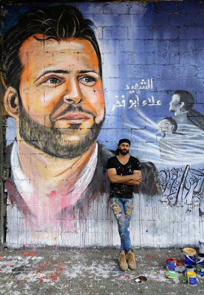 Ghayath al-Rawbeh, a Palestinian refugee, painted a mural of Lebanese protester Alaa Abou Fakhr, who was shot dead south of Beirut (AFP Photo/Ibrahim CHALHOUB)