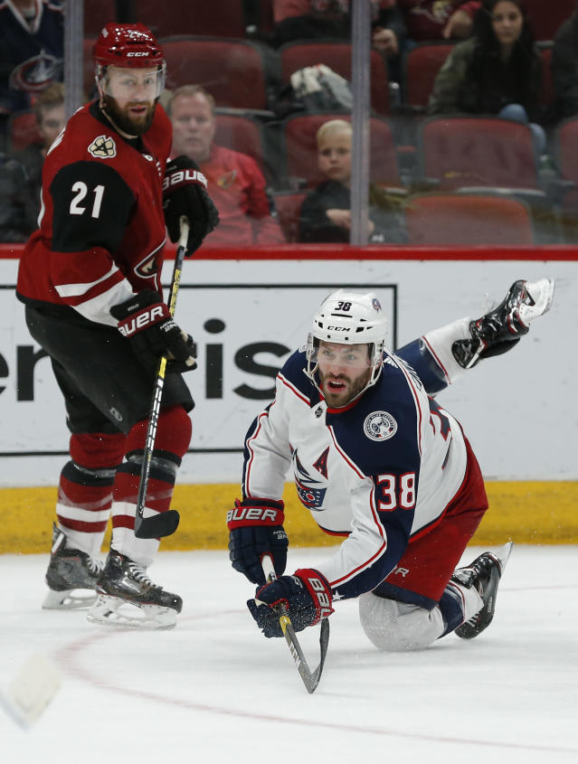 Columbus Blue Jackets center Boone Jenner (38) scores a goal in front of Arizona Coyotes center Derek Stepan during the third period during an NHL hockey game Thursday, Feb. 7, 2019, in Glendale, Ariz. Columbus won 4-2. (AP Photo/Rick Scuteri)