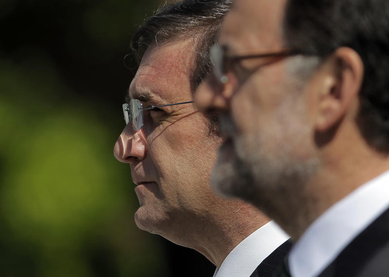 Spain's Prime Minister Mariano Rajoy, foreground and Portugal's Prime Minister Pedro Passos Coelho, left, review troops during a welcome ceremony, prior to  a meeting at the Moncloa Palace, in Madrid, Monday, May 13, 2013. (AP Photo/Andres Kudacki)