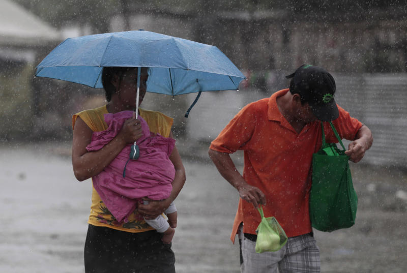 A Filipino woman holds a baby during a brief rainfall in Manila, Philippines on Monday, Aug. 12, 2013. Powerful Typhoon Utor battered the northern Philippines on Monday, toppling power lines and dumping heavy rains across mountains, cities and food-growing plain. The storm killed at least one man in a landslide and left 45 fishermen missing. (AP Photo/Aaron Favila)