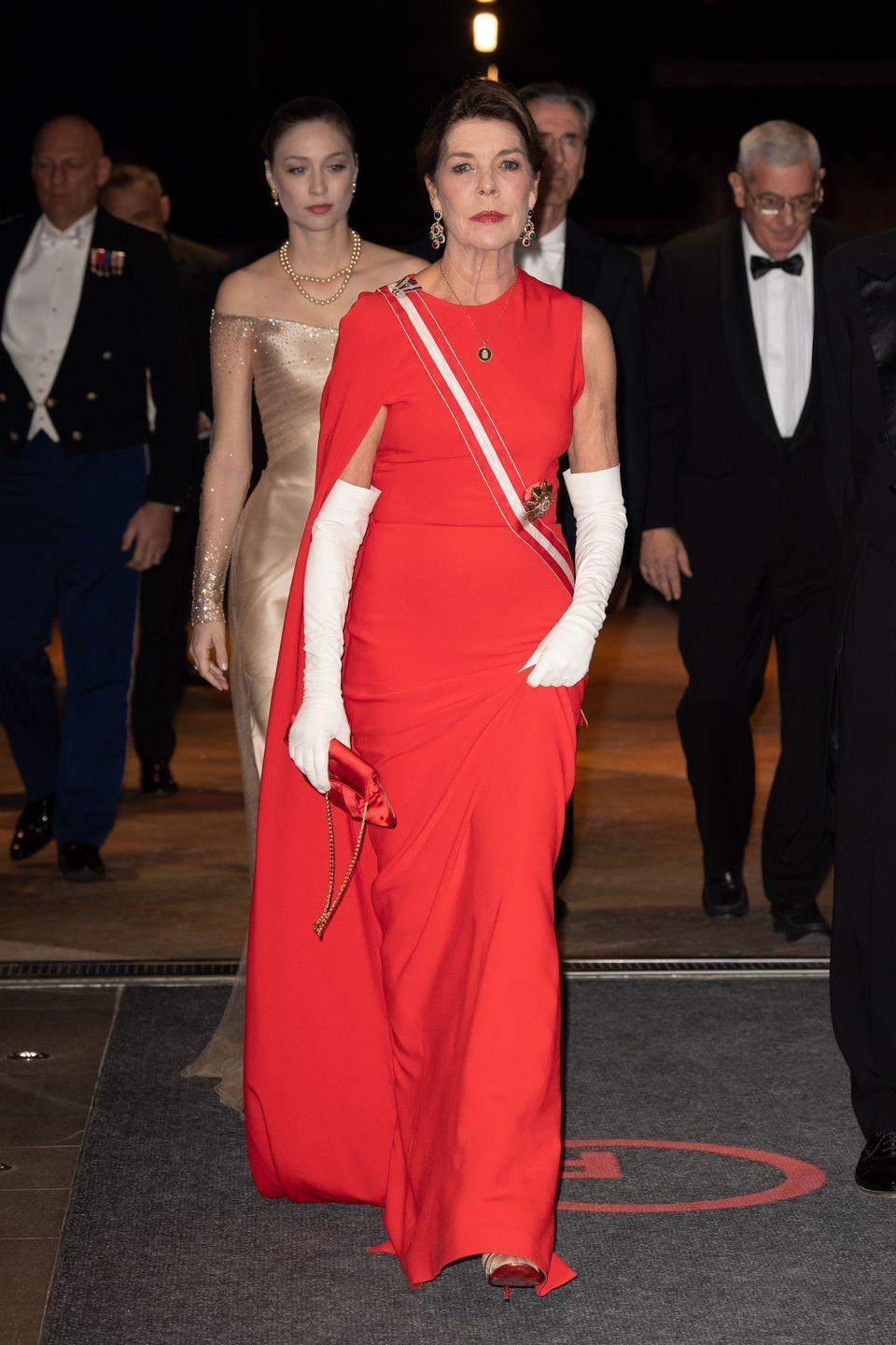 <p>The Monaco royal wore the same asymmetrical Stella McCartney cape dress for 2018's Monaco National Day gala. Princess Caroline paired the gown with long white gloves and a red satin purse. <br></p>