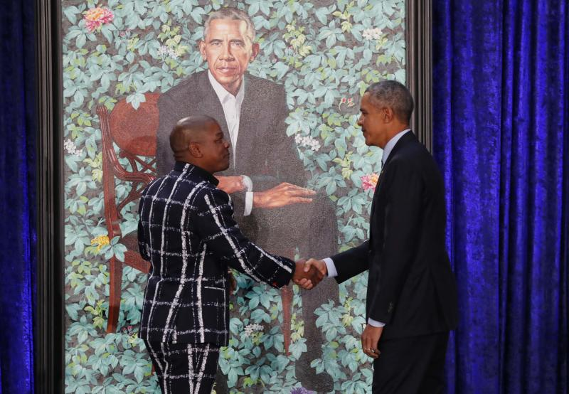 Former U.S. President Barack Obama greets artist Kehinde Wiley during the unveiling of his portrait at the Smithsonian's National Portrait Gallery in Washington, U.S., February 12, 2018. REUTERS/Jim Bourg