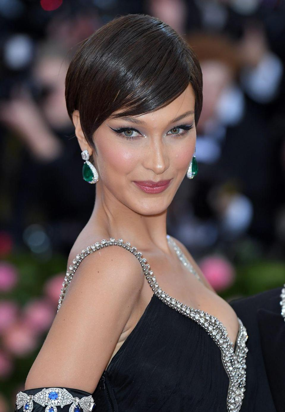 <p>Bella Hadid's Moschino Met Gala look wasn't complete without a side-parted and ultra-glossy pixie cut (it was a very well done wig).</p>