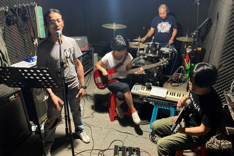 Noodles shop owner and a rock band singer Wang Zongxing rehearses with his band at a studio in Shenzhen