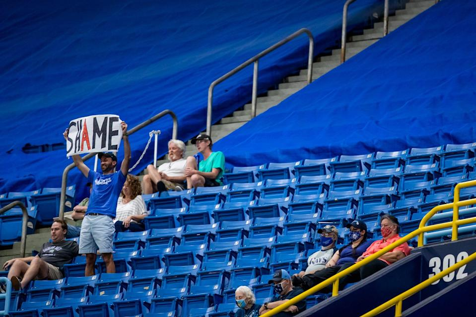 A Rays fan holds a sign referencing the Astros' sign-stealing scandal at Tropicana Field.