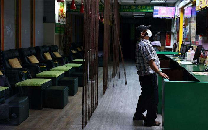 A man wearing a protective face mask stands at a closed massage shop after several venues were ordered to close amid an increasing number of COVID-19 infections, in Taipei, Taiwan - ANN WANG / REUTERS