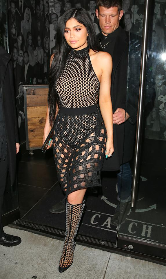 <p>Jenner was spotted grabbing dinner in Los Angeles looking like a sexy beehive. For the outing, she opted for a sheer mesh bodysuit and coordinating skirt that she paired with honeycomb Tamara Mellon over-the-knee boots.</p>
