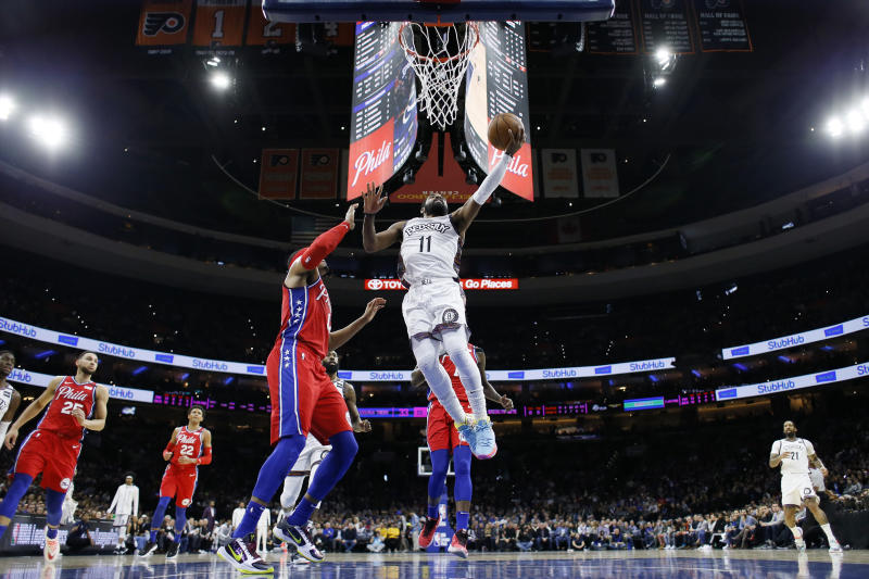 Brooklyn Nets' Kyrie Irving, right, goes up for a shot against Philadelphia 76ers' Tobias Harris during the first half of an NBA basketball game, Wednesday, Jan. 15, 2020, in Philadelphia. (AP Photo/Matt Slocum)
