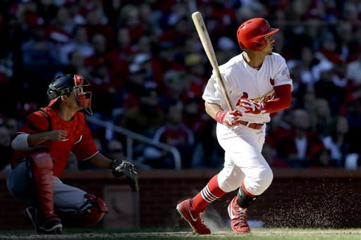 St. Louis Cardinals' Jon Jay hits a sacrifice fly to score Daniel Descalso as Washington Nationals catcher Kurt Suzuki, left, watches during the second inning in Game 1 of baseball's National League division series, Sunday, Oct. 7, 2012, in St. Louis. (AP Photo/Jeff Roberson)