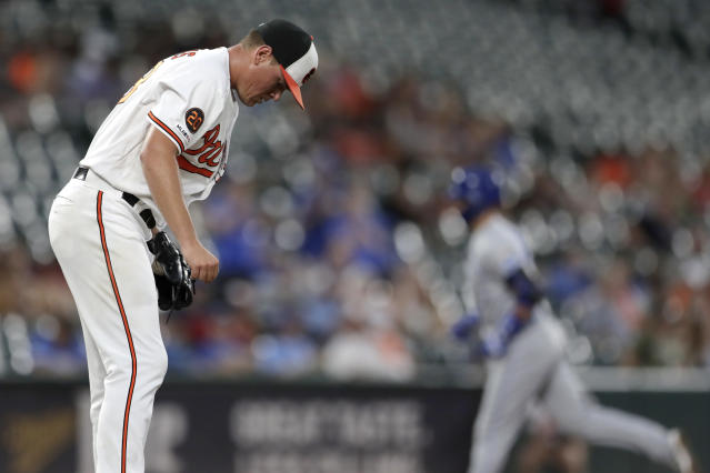 Baltimore Orioles starting pitcher Aaron Brooks, left, reacts after allowing a solo home run to Kansas City Royals' Whit Merrifield, right, during the third inning of a baseball game, Wednesday, Aug. 21, 2019, in Baltimore. (AP Photo/Julio Cortez)