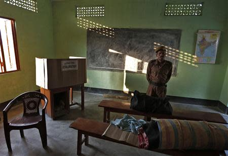 A policeman stands guard over an Electronic Voting Machine (EVM) at a polling booth ahead of the general elections in Majuli, a large river island in the Brahmaputra river, Jorhat district, in the northeastern Indian state of Assam April 6, 2014. REUTERS/Adnan Abidi