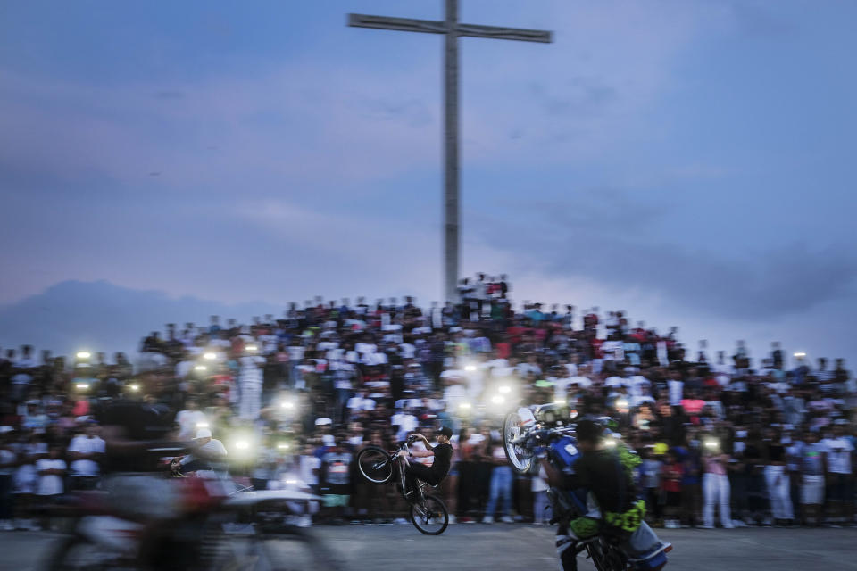 A youth performs a wheelie on his bike during an exhibition in the Petare neighborhood of Caracas, Venezuela, Sunday, Sept. 19, 2021. (AP Photo/Matias Delacroix)