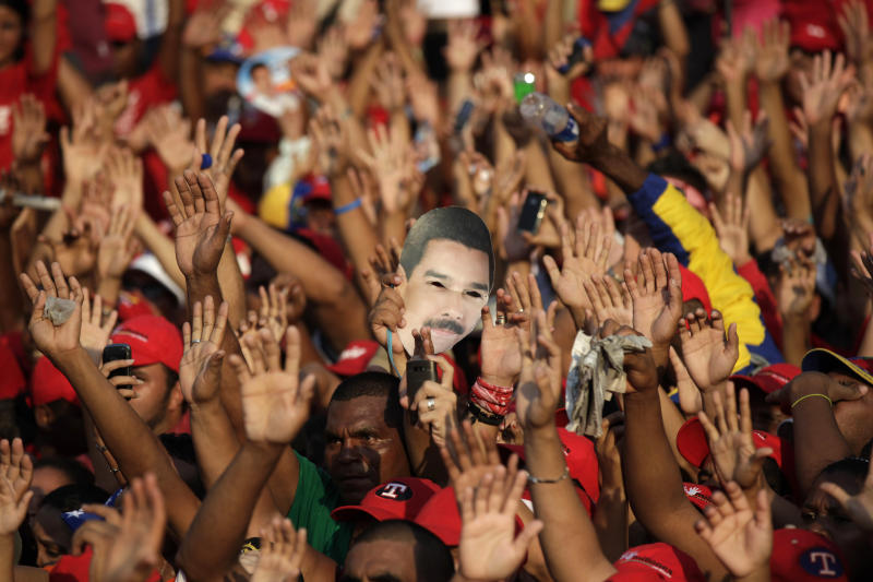 Supporters wave their hands as one of them holds a mask of Venezuela's acting President Nicolas Maduro during a campaign rally in Catia La Mar, Venezuela, Tuesday, April 9, 2013. Maduro, the hand-picked successor of late President Hugo Chavez, is running for president against opposition candidate Henrique Capriles in the presidential election set for Sunday, April 14. (AP Photo/Ariana Cubillos)
