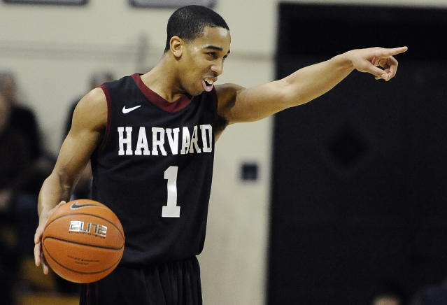Harvard's Siyani Chambers, points and smiles at his team as he dribbles in the final seconds of an NCAA college basketball game against Yale, Friday, March 7, 2014, in New Haven, Conn. Harvard won 70-58. (AP Photo/Jessica Hill)