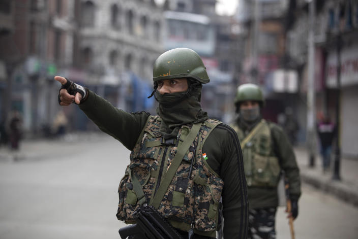 An Indian paramilitary officer points towards civilians as they patrol a closed market in Srinagar, Indian controlled Kashmir, Tuesday, Feb. 9, 2021. Businesses and shops have closed in many parts of Indian-controlled Kashmir to mark the eighth anniversary of the secret execution of a Kashmiri man in New Delhi. Hundreds of armed police and paramilitary soldiers in riot gear patrolled as most residents stayed indoors in the disputed region's main city of Srinagar. (AP Photo/Mukhtar Khan)