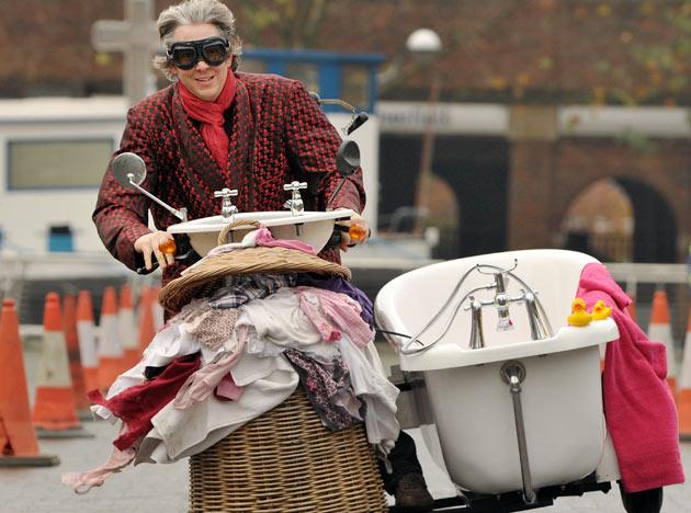 British inventor Edd China rides the worlds fastest toilet with a top speed of 68km/h during a race at the annual Guinness World Records Day in London on November 17, 2011. Wacky Guinness world record holders got together to race their unlikely vehicles like the world's fastest toilet and smallest roadworthy car in London the mark the 7th annual Guinness World Records day.  AFP PHOTO / BEN STANSALL