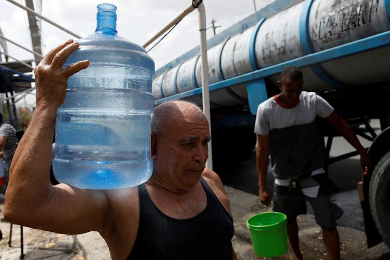 Men carry containers filled with water from a tank truck in the municipality of Canovanas, Puerto Rico, on Sept. 26. (Carlos Garcia Rawlins/Reuters)