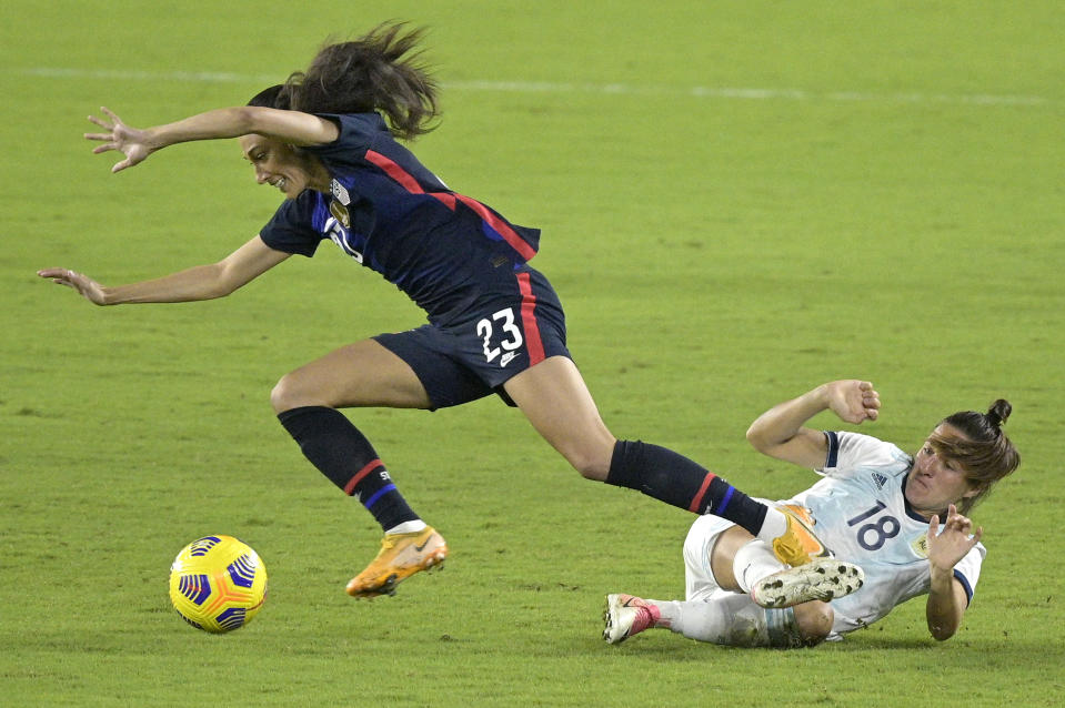 CORRECTS DATE United States forward Christen Press (23) and Argentina defender Romina Nunez (18) collide while going for a ball during the first half of a SheBelieves Cup women's soccer match, Wednesday, Feb. 24, 2021, in Orlando, Fla. (AP Photo/Phelan M. Ebenhack)