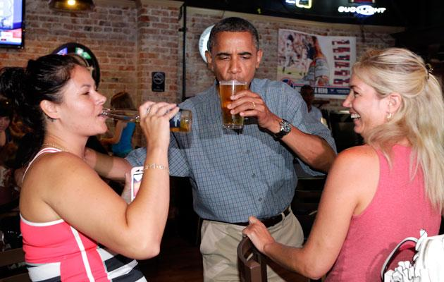 U.S. President Barack Obama enjoys a beer with Jennifer Klanac (L) and Suzanne Woods (R) at Ziggy's Pub in Amherst, Ohio July 5, 2012. Obama is on a two-day campaign bus tour of Ohio and Pennsylvania.