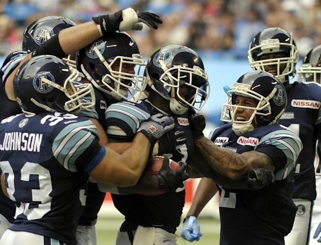 Toronto Argonauts' Cory Boyd, with ball, is congratulated by teammates after scoring a touchdown during 1st half CFL action against the Calgary Stampeders in Toronto, Saturday, July 7, 2012. (CFL PHOTO - J.P. Moczulski)