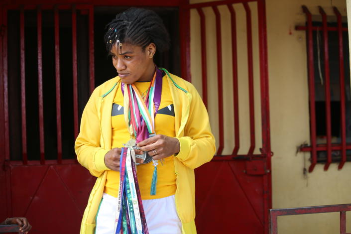 Guinean wrestler Fatoumata Yarie Camara holds past credentials and medals at her house in Conakry, Guinea, Monday July 19, 2021. A West African wrestler's dream of competing in the Olympics has come down to a plane ticket. Fatoumata Yarie Camara is the only Guinean athlete to qualify for these Games. She was ready for Tokyo, but confusion over travel reigned for weeks. The 25-year-old and her family can't afford it. Guinean officials promised a ticket, but at the last minute announced a withdrawal from the Olympics over COVID-19 concerns. Under international pressure, Guinea reversed its decision. (AP Photo/Youssouf Bah)