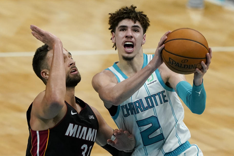 LaMelo Ball with the ball in his hands going against Max Strus toward the basket. Ball's mouth is open in a yelling manner, while Strus has one arm raised to defend.