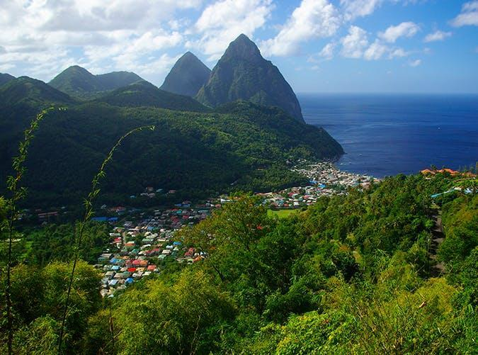 """<p>Sure, there are plenty of stunning <a href=""""https://www.purewow.com/travel/Best-Caribbean-Vacations"""" rel=""""nofollow noopener"""" target=""""_blank"""" data-ylk=""""slk:Caribbean destinations"""" class=""""link rapid-noclick-resp"""">Caribbean destinations</a>, but the view of the Piton Mountains overlooking the colorful town of Soufrière is something you've gotta see for yourself.</p>"""