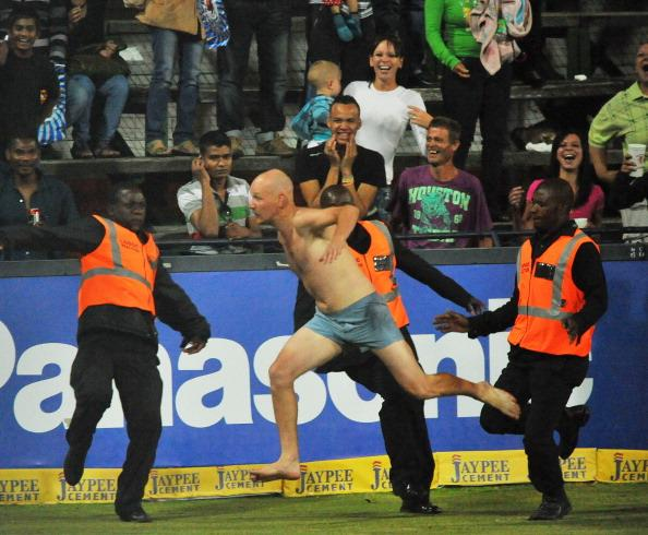JOHANNESBURG, SOUTH AFRICA - OCTOBER 14:  A pitch invader is tackled by security staff during the Karbonn Smart CLT20 match between Highveld Lions and Mumbai Indians at Bidvest Wanderers Stadium on October 14, 2012 in Johannesburg, South Africa.  (Photo by Duif du Toit/Gallo Images/Getty Images)