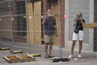 People take pictures as construction work continues on damaged buildings on 2nd Avenue North Friday, June 25, 2021, in Nashville, Tenn. Six months after a Christmas Day bombing ripped a hole in historic downtown, workers continue to chip away at cleanup efforts so that revitalization can begin. The tediously slow process has meant workers haven't been able to access some of the buildings until recent weeks. (AP Photo/Mark Humphrey)