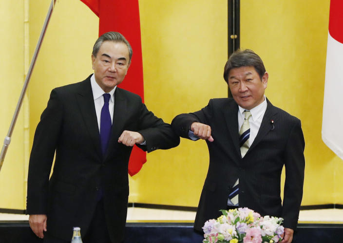China' Foreign Minister Wang Yi, left, and his Japanese counterpart Toshimitsu Motegi bump elbows as they meet amid the coronavirus outbreak, in Tokyo on Tuesday, Nov. 24, 2020. Wang met Motegi on Tuesday to discuss ways to revive their pandemic-hit economies as well as regional concerns over China's growing influence. (Issei Kato/Pool Photo via AP)
