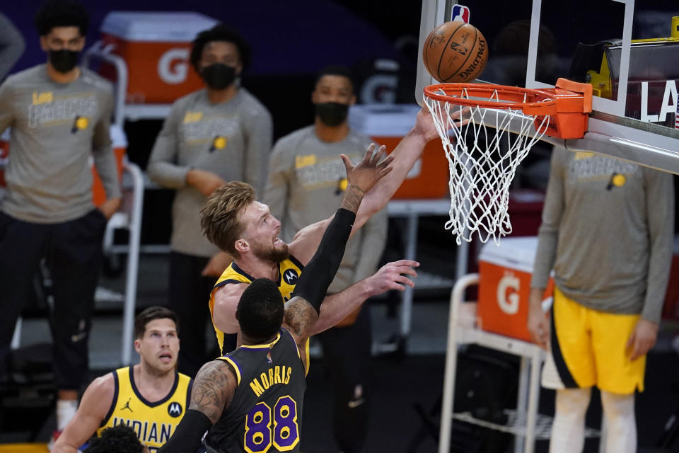 Indiana Pacers forward Domantas Sabonis, top, scores over Los Angeles Lakers forward Markieff Morris (88) during the first half of an NBA basketball game Friday, March 12, 2021, in Los Angeles. (AP Photo/Marcio Jose Sanchez)