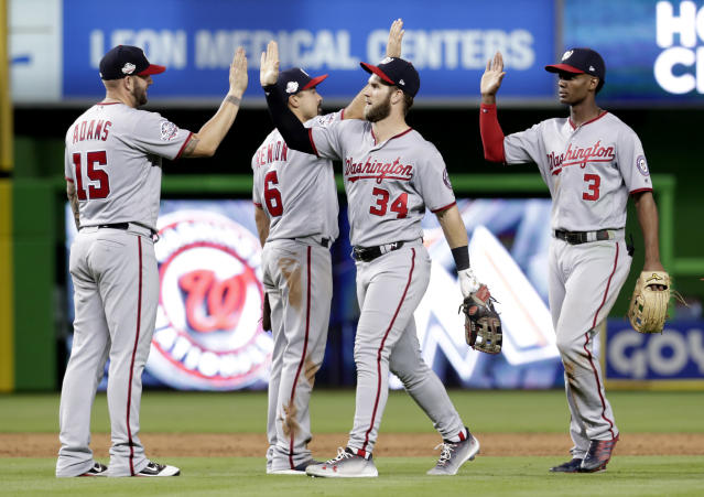 Washington Nationals first baseman Matt Adams (15), third baseman Anthony Rendon (6), right fielder Bryce Harper (34) and center fielder Michael Taylor (3) high-five after a baseball game against the Miami Marlins, Friday, May 25, 2018, in Miami. (AP Photo/Lynne Sladky)