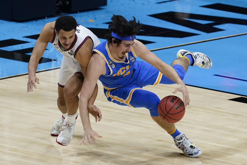 UCLA guard Jaime Jaquez Jr. fights for a loose ball with Gonzaga guard Jalen Suggs, left, during the first half of a men's Final Four NCAA college basketball tournament semifinal game, Saturday, April 3, 2021, at Lucas Oil Stadium in Indianapolis. (AP Photo/Darron Cummings)