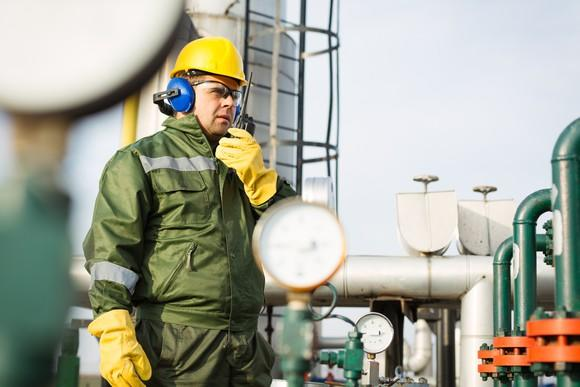 A man wearing a hard hat, safety glasses, and headphones standing in front of pipeline infrastructure and speaking into a walkie-talkie