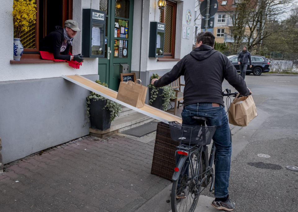 A man on a bike picks up food to go in front of the apple cider restaurant 'Zum Lahmen Esel' in Frankfurt, Germany, Friday, April 3, 2020. Due to the coronavirus outbreak the restaurant which has been in operation since 1807 offers cider and food to go in a self-made drive through set up.(AP Photo/Michael Probst)